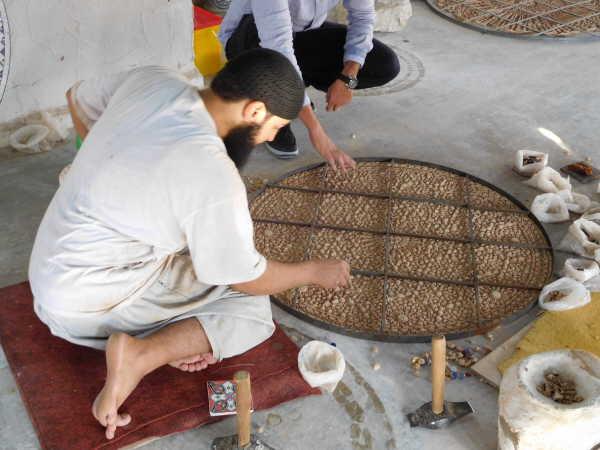 craftsman placing mosaic tiles